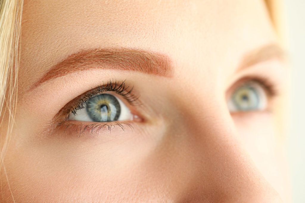Attraktiv ung kvinne med blå øyne og permanent bryn