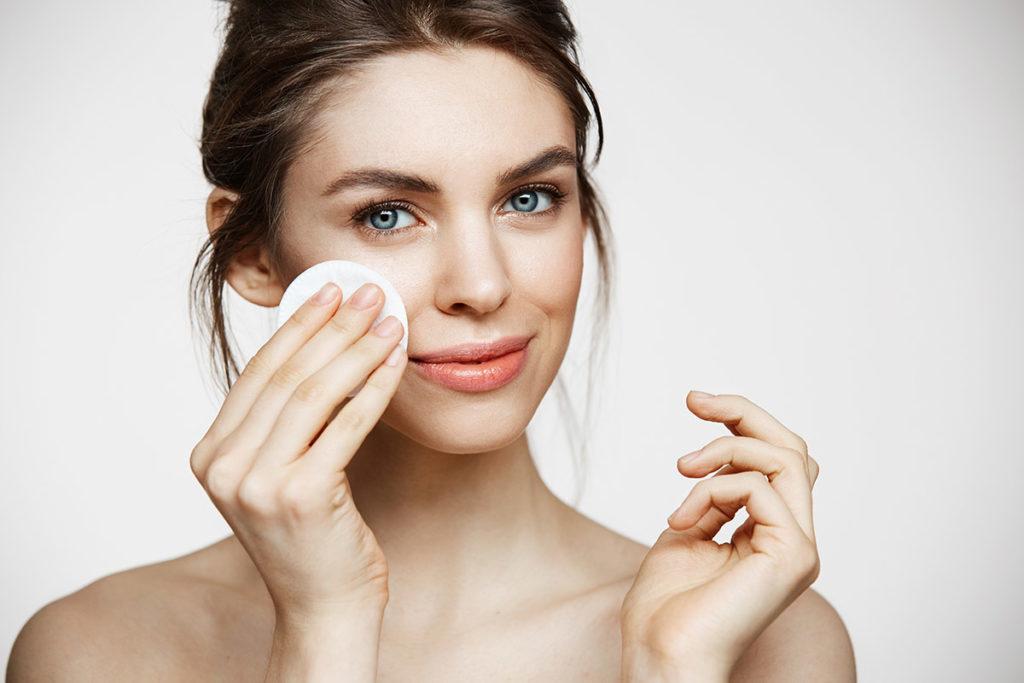 Attraktiv ung kvinne med blå øyne og brunt hår som vasker ansiktet sitt med en pad, hudpleie