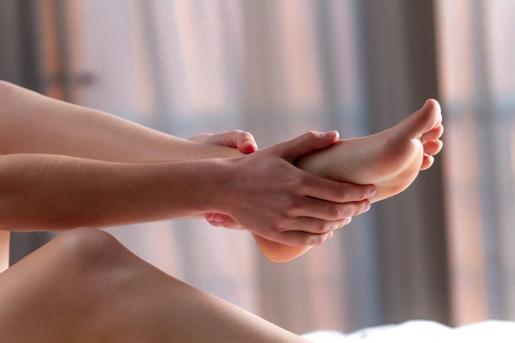 Kvinne som holder opp foten sin